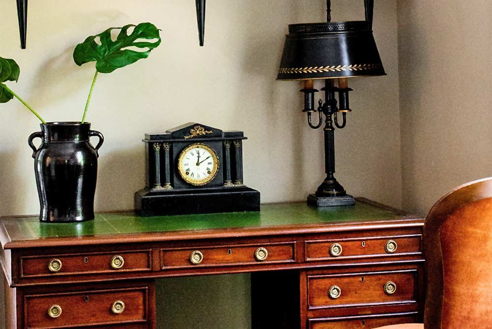 Potter, clock, and lamp on a vintage style desk