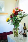 Flower arangment and a bottle of wine with glasses