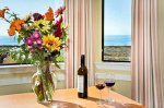 Flower arengment on a table with some wine