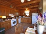 A spacious kitchen with oven, dishwasher, fridge, and other appliances