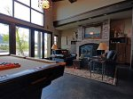 A pool table and sitting area with fireplace