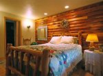 A bed in a cozy log cabin room