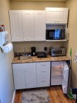 Kitchenette with fridge, sink, microwave, condiments, toaster oven, hot plate and coffee machine