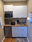 Kitchenette with fridge, toaster oven, hot plate, condiments, microwave and coffee machine