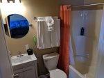 Washroom with sink, toilet, mirror and bath tub with shower
