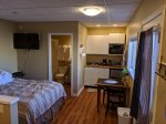 Overview of room showing bed, large tv, washroom, kitchenette and dining table with chairs